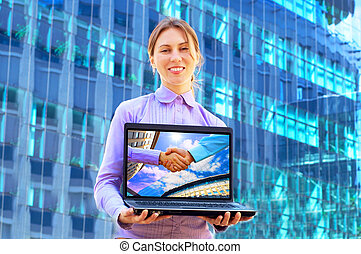 Happiness business woman with laptop on blured background