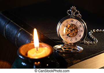 Watch And Candle - Vintage pocket watch on book near...