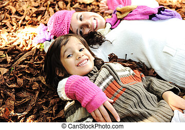 Cute boy lying in the Autumn fall leaves with his mother