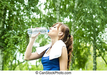 Young woman drinking water after exercise, summer park...
