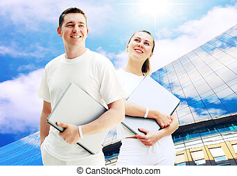 Pair of two happy young people or student with laptops on...
