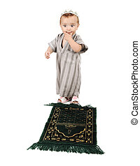 little muslim kid is praying on traditional way and thinkig how