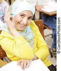 Cute Muslim arabic girl sitting on the chair and holding pencil - at school