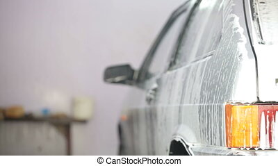 car in soap foam at carwash