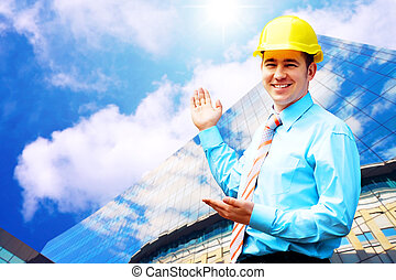 Young architect wearing a protective helmet standing on the...