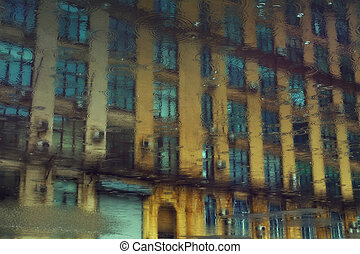 Reflection of urban building in a puddle of rain with the...