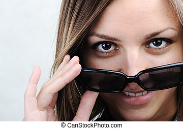 Beauty woman wearing sunglasses on tip of nose and smiling