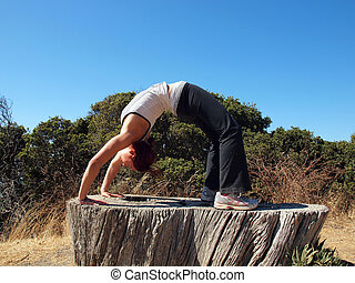 Attractive 20-something lady does a backbend on old tree...