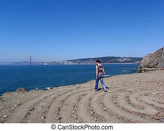 Attractive 20-something walks out to lands end of a stone path with the Golden Gate Bride in the background