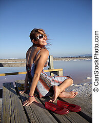 Attractive 20-something lady wearing sunglasses, earings and...