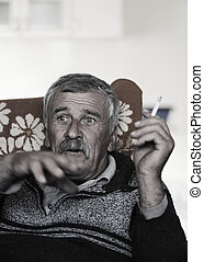Old man with mustache smoking cigarette while sitting in...
