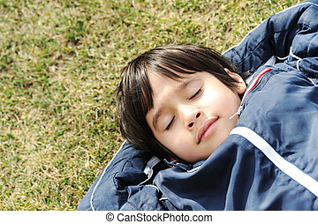 Happy dreaming child on green meadow