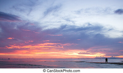 Romantic sunset - Silhouettes of romantic couple on a beach...