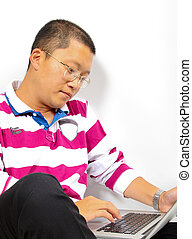 Young chinese man sitting with a laptop