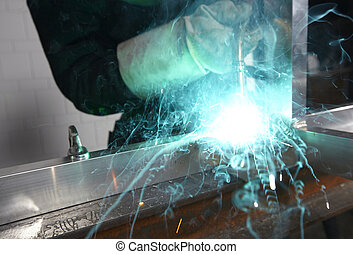 Welder with sparks arcing in a cyan light