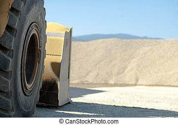 Tire backhoe close-up and piles of sand background