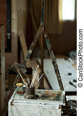 Easel and paint brushes in artistic workshop