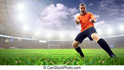 Happiness football player after goal on the stadium with light