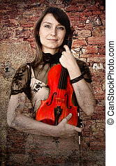 Beautiful female violinist with violin on the grunge...