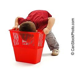 Little boy looking deep into garbage bin