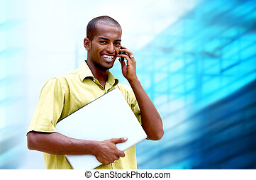Young happy man or student with laptop and phone on the...