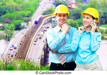 Young architects wearing a protective helmet standing on the...