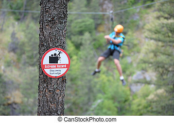 Extreme Zip-Lining - A sign for extreme danger with a...
