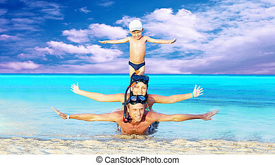 Happy young couple and son with snorkeling on a sea beach