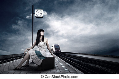Girl waiting train on the platform of railway station