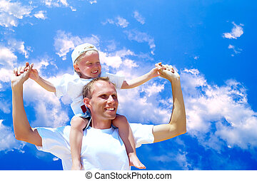 Joyful father giving piggyback ride to his son against a sky...