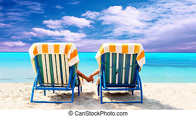 Rear view of a couple on a deck chair relaxing on the beach