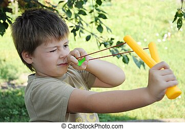 A boy plays with a left-handed catapult