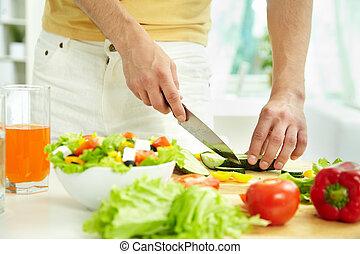 Cutting cucumber - Close-up of male cutting cucumber while...