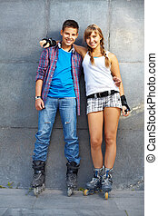 Youthful dates - Couple of happy roller skaters looking at...