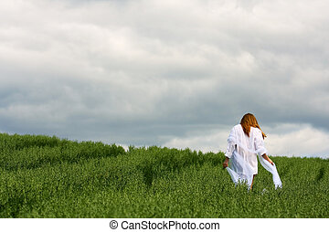 Lonely woman in a field - Young woman walking in an oats...