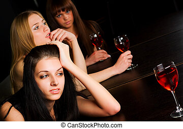 Three young women in a bar - Three young women drinking red...