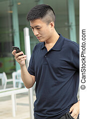 Asian man typing a message on mobile phone.
