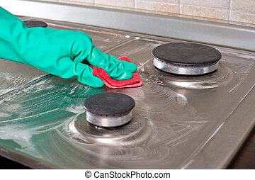Housework - Hand in green protective glove cleans a...