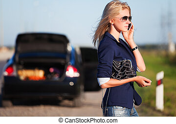 Young woman calling for help - Young blond with a broken car...