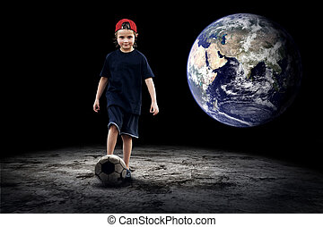 Child football player and Grunge ball on the dark background