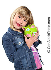 Little girl holding a green piggy bank