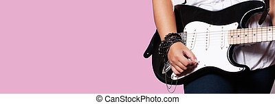 Closeup of girl playing on guitar on pink background