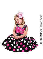 Little girl in a pretty pink dress with polka dots