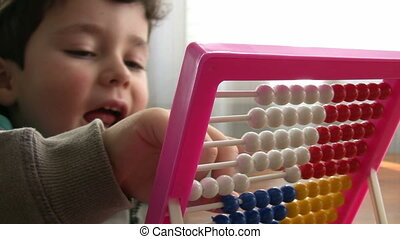 Little Boy using abacus - Preschool student learning...
