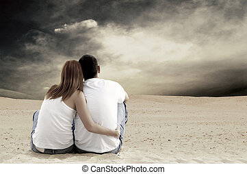 Young couple seating in desert in sunny day