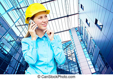 Young architect-woman wearing a protective helmet standing...