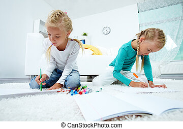 Twins drawing - Portrait of twin girls drawing at home