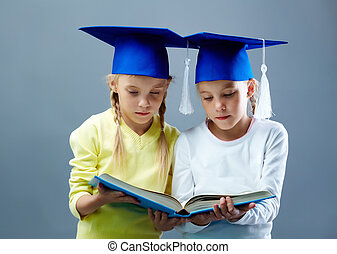 Twins reading - Portrait of lovely twin girls in hats with...