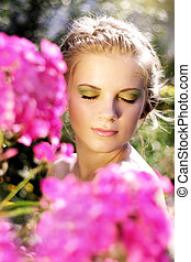 Young woman with summer make-up. pink phlox flowers