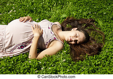 Beautiful pregnant woman relaxing in the park - Beautiful...